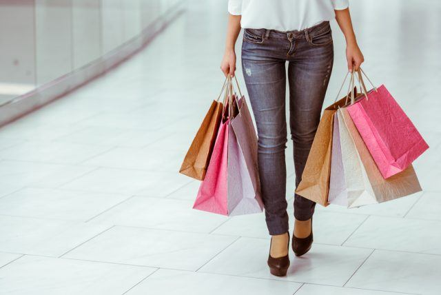 woman in white blouse and jeans holding shopping bags