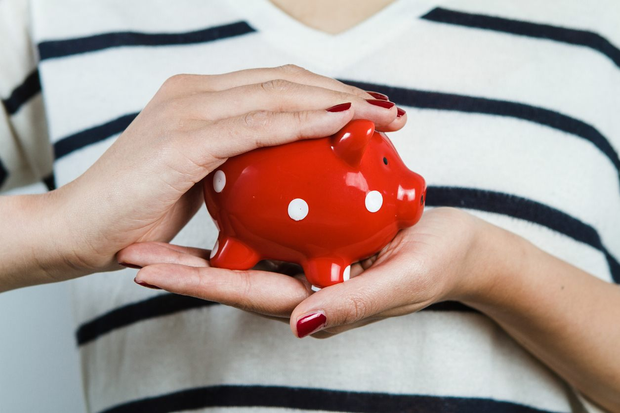 Woman holding red piggy bank