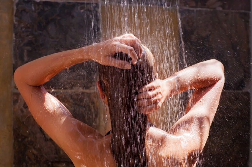 back side of young female showering under refreshing water