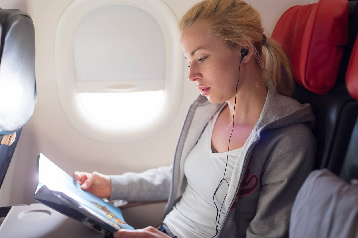 Woman reading magazine and listening to music on airplane
