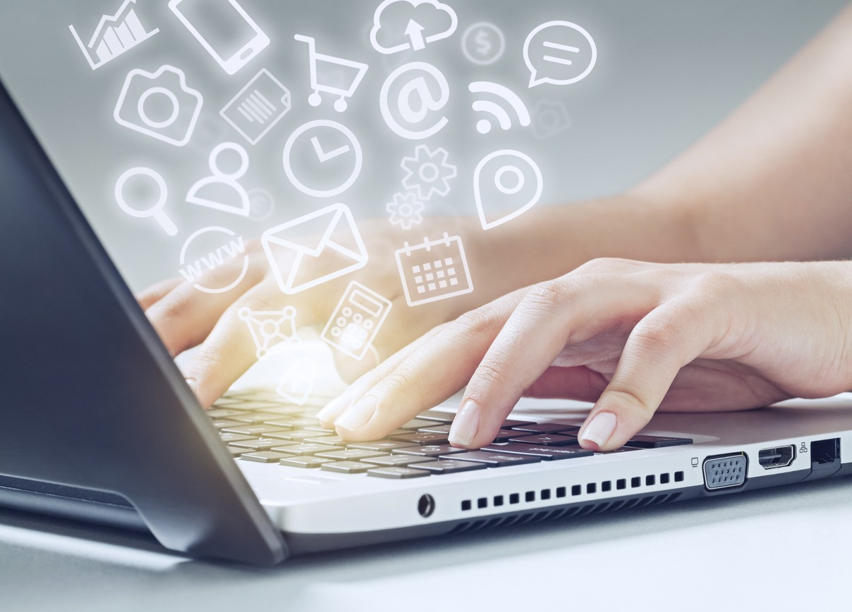 woman typing on laptop computer and media app icons flying