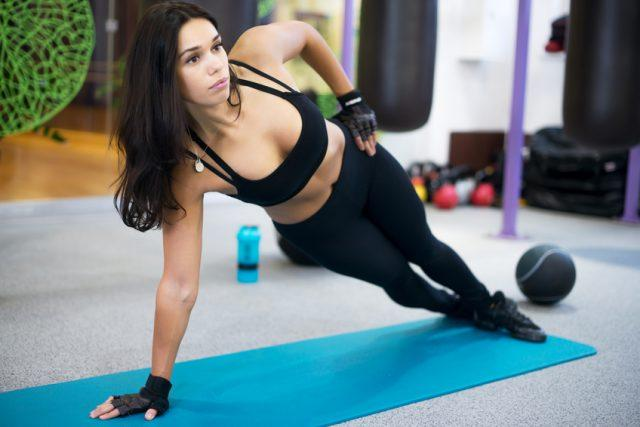 Fit woman doing side plank yoga pose