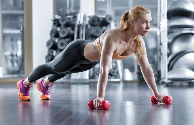 woman doing push-ups with weights in her hands in the gym