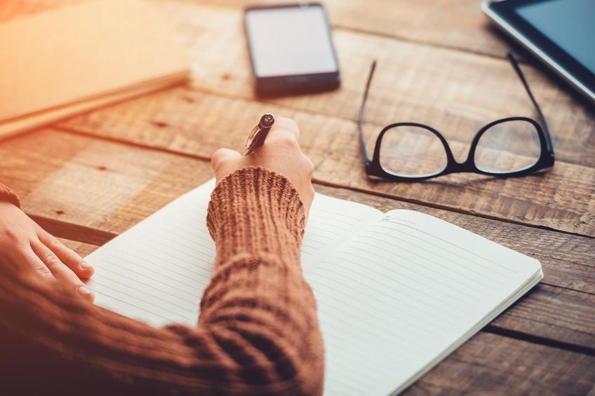 image of woman writing, working