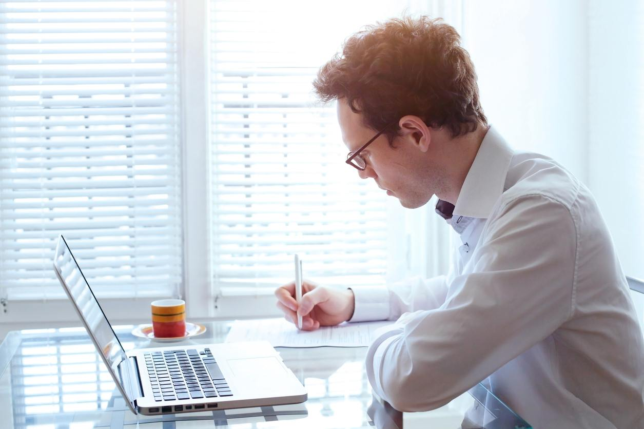 man writing with laptop