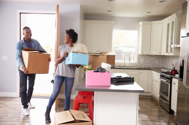 Young couple moving boxes into their new home