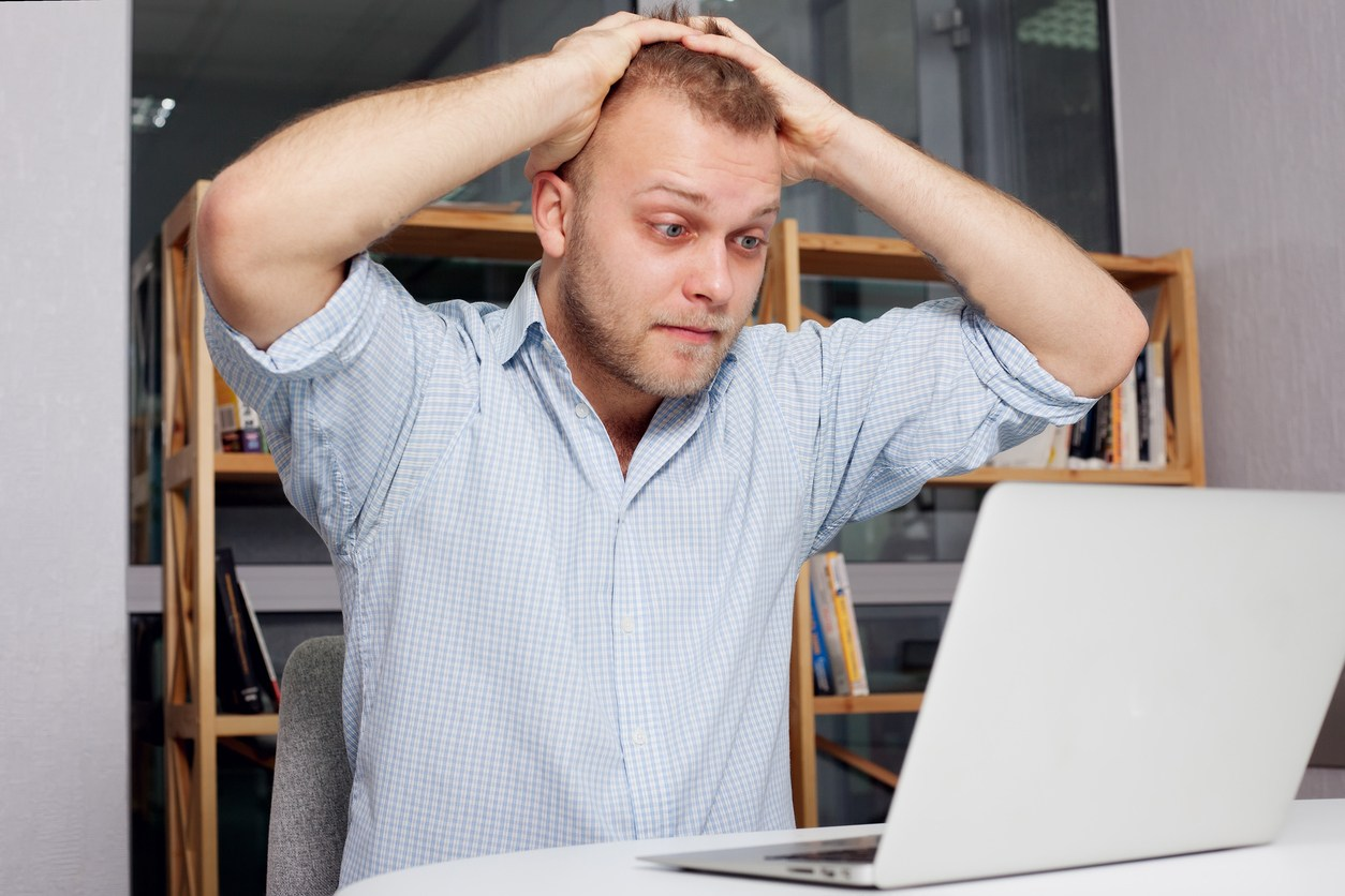 businessman at his desk looking fearfully looking at a laptop