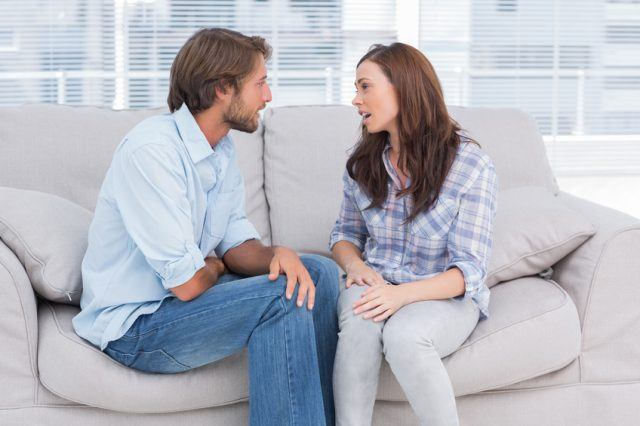 A couple sits on a couch having a conversation.
