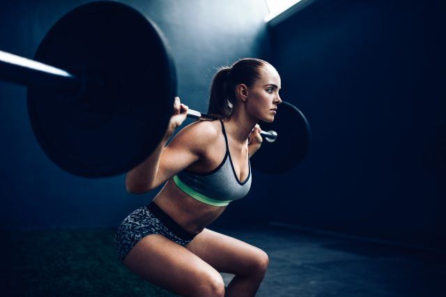 female athlete doing squat with barbell