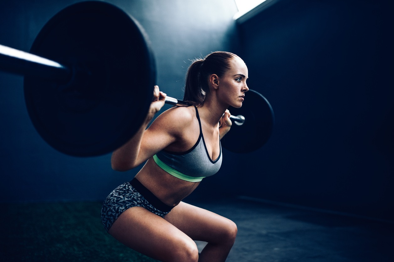 Athlete demonstrates a squat with a barbell