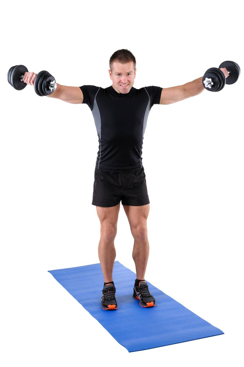 An instructor shows the finishing position of a standing dumbbell lateral raise