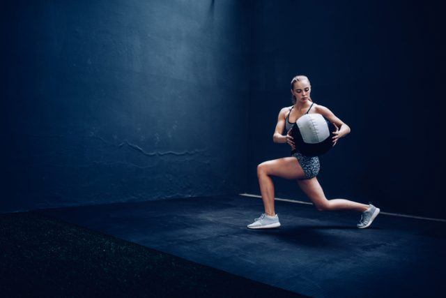 woman doing exercises with medicine ball in a gym