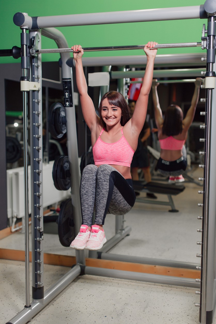 woman doing abs exercises while hanging from a bar