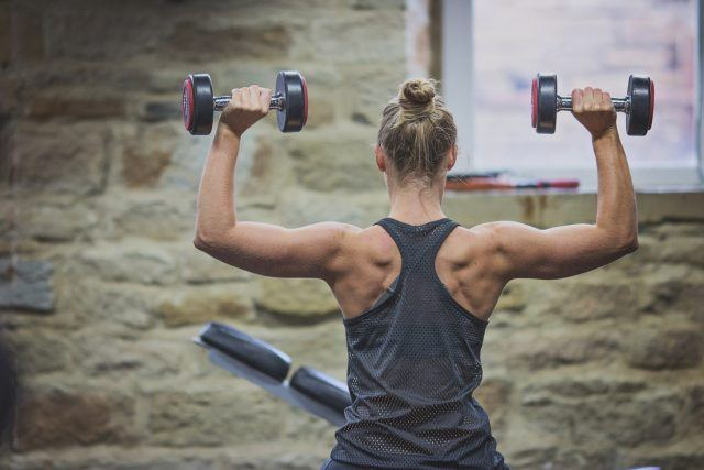 Woman holding dumbells above her head.