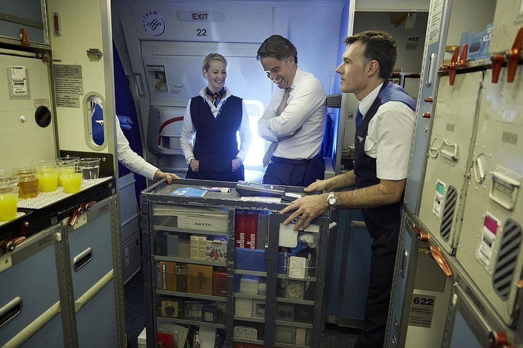 Flight attendants walk around the airplane with a gift cart