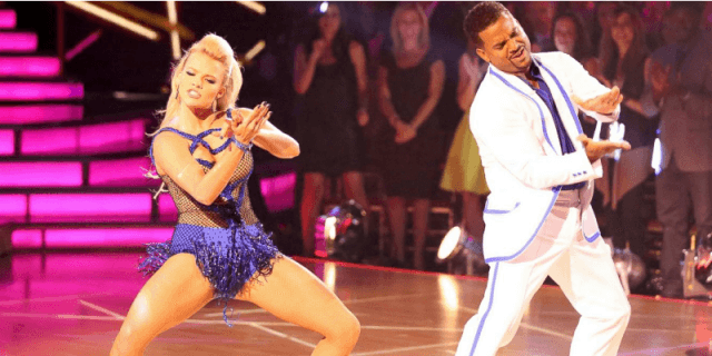 Alfonso Ribeiro dances in a white suit next to his partner on the dance floor.