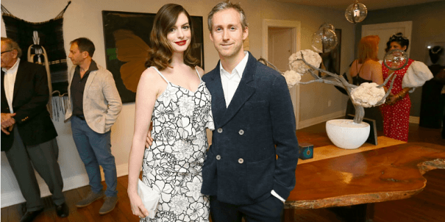 Anne Hathaway and Adam Shulman holding each other as they smile.