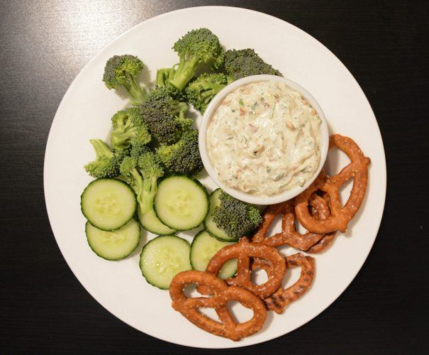 overhead shot of a plate filled with veggies, pretzels, and bacon and charred scallion dip