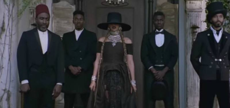 Beyonce is in a black dress and black hat while standing on a porch surrounded by men in suits.