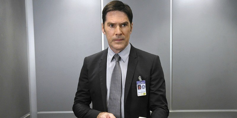 Thomas Gibson rides an elevator and dons a badge in a scene from Criminal Minds