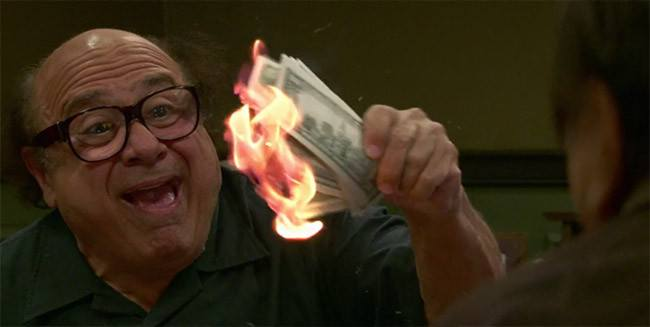 Frank Reynolds, portrayed by Danny DeVito, lights cash on fire in an episode of FX's It's Always Sunny in Philadelphia