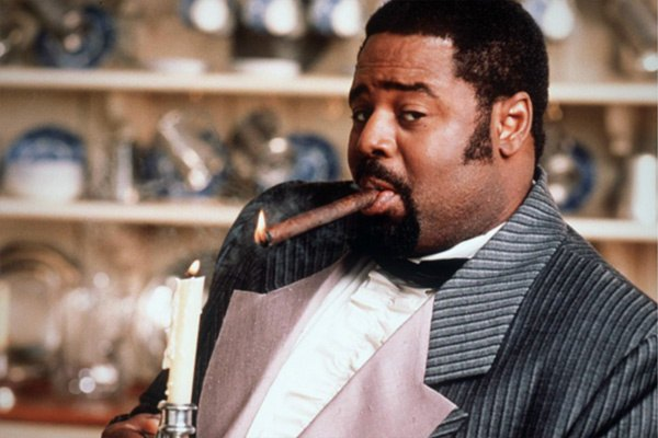 Chi McBride smokes a cigar and holds a candle in a scene from The Secret Diary of Desmond Pfeiffer