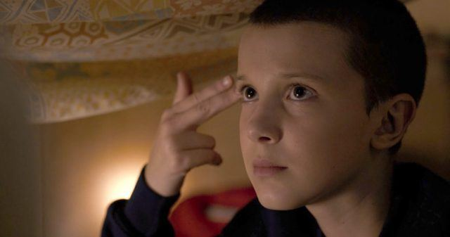 Millie Bobby Brown as Eleven in 'Stranger Things' holding two fingers up to her forehead.