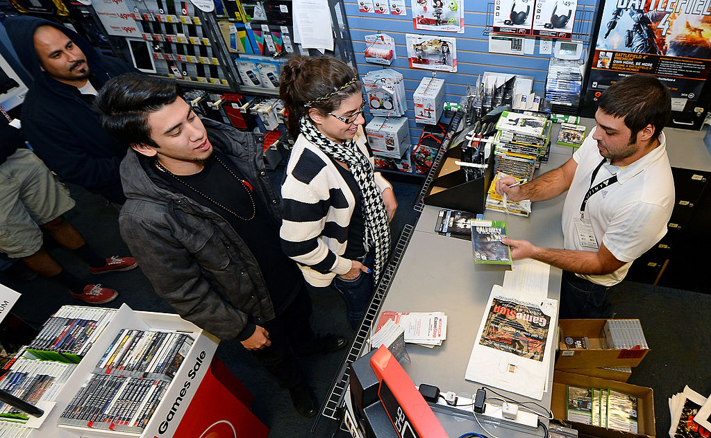 A store manager sells copies of Call of Duty: Ghosts during GameStop's hayday