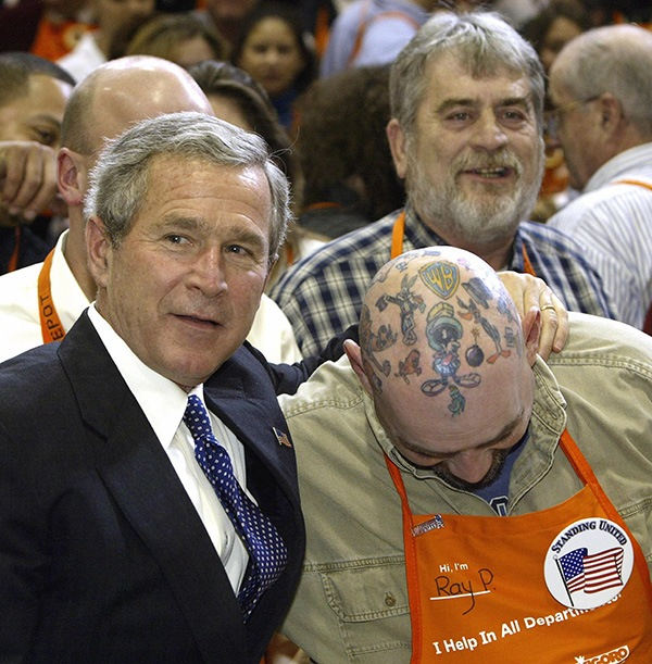 George W. Bush posing with a guy who has head tattoos