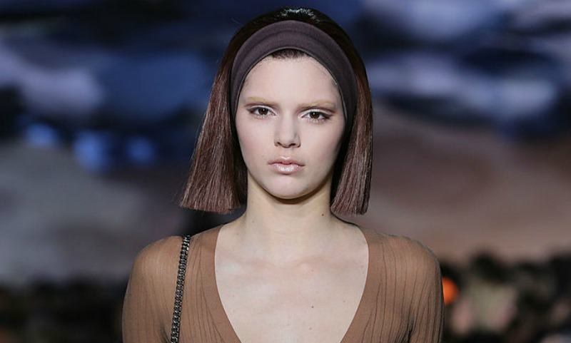 Kendall Jenner in a tan top with a blunt short haircut walking the runway