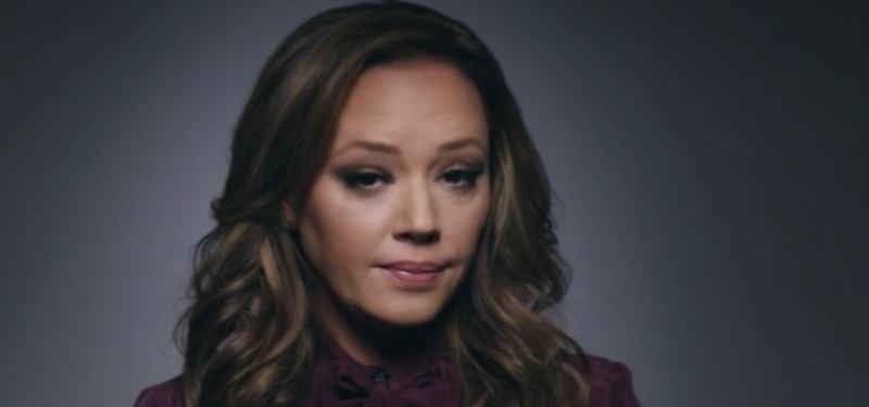 Leah Remini looks directly at the camera seriously in front of a dark background