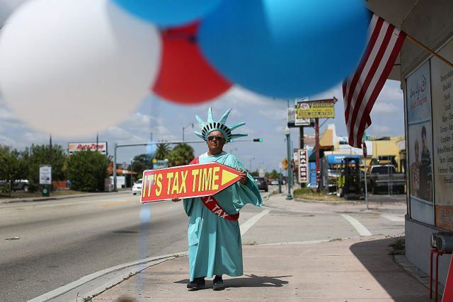 "Person dressed like Statue of Liberty holding sign that says, ""It's tax time."""