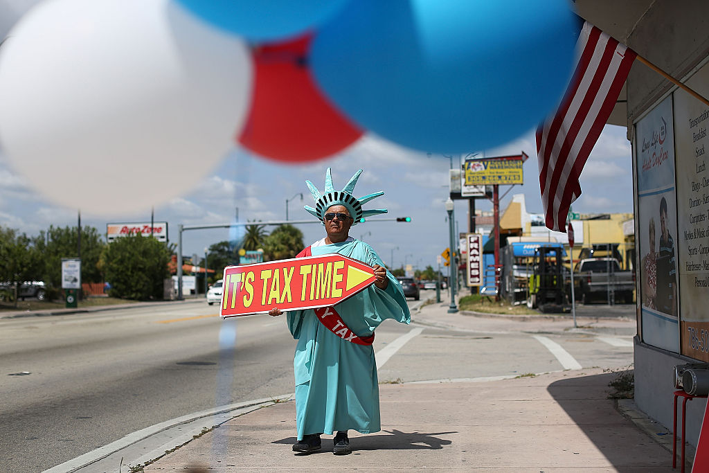 "person dressed as Statue of Liberty waving ""it's tax time"" sign"
