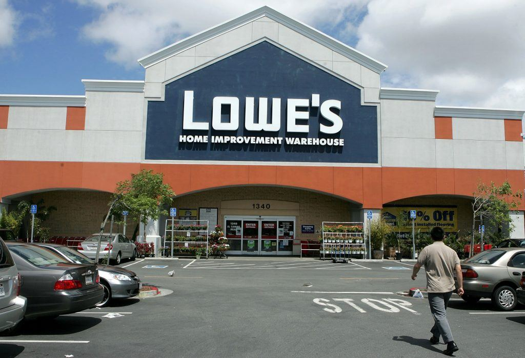 A man walks toward the entrance of a Lowe's store