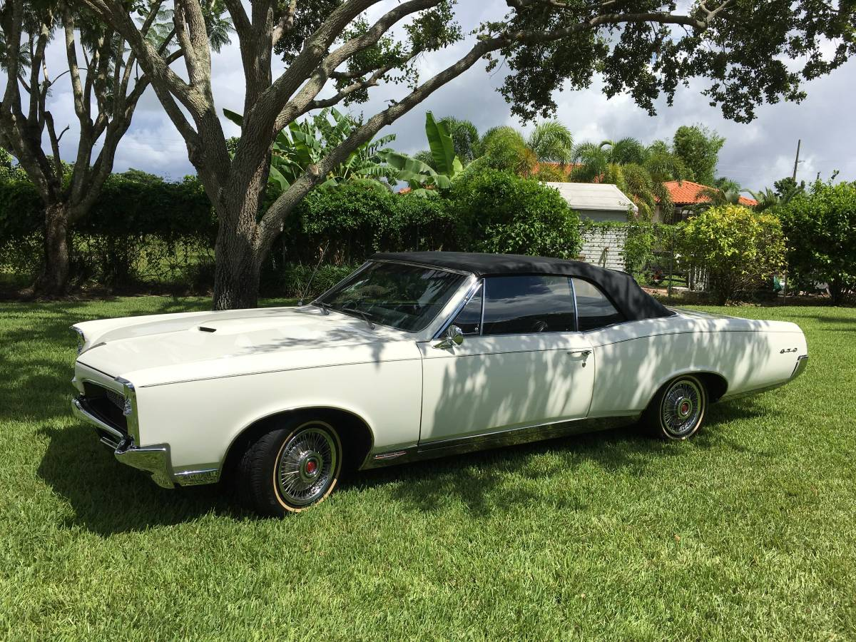 White 1967 Pontiac GTO convertible parked on the grass under a tree