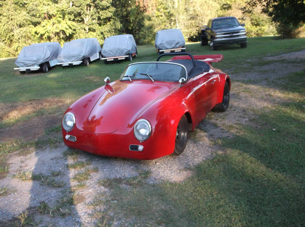 Red 1957 Porsche 356 replica parked on a grassy area.