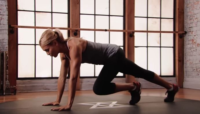 Fitness trainer demonstrates how to perform an ab exercise