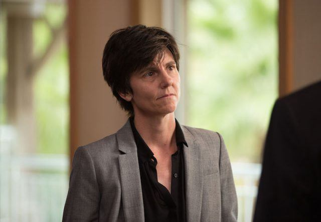 Tig wearing a black shirt and gray blazer.
