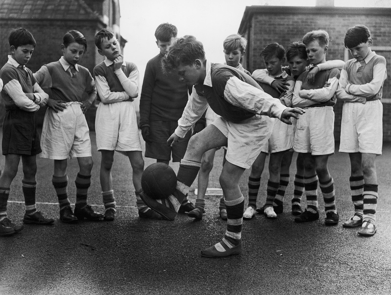 A young stand out demonstrates his ball skills to team-mates during after-school football practice in 1950s England