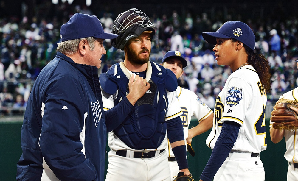Two baseball players and their coach talk to each other on the field in a crowded stadium in a scene from Pitch