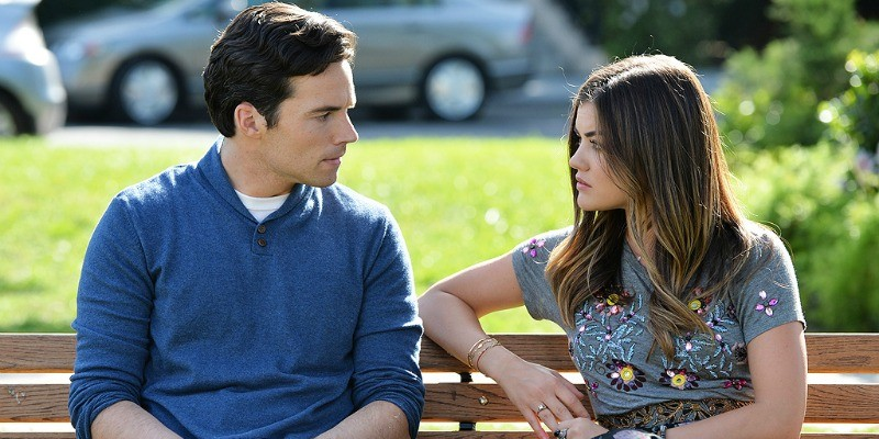 Aria and Fitz are sitting on a park bench talking on Pretty Little Liars.