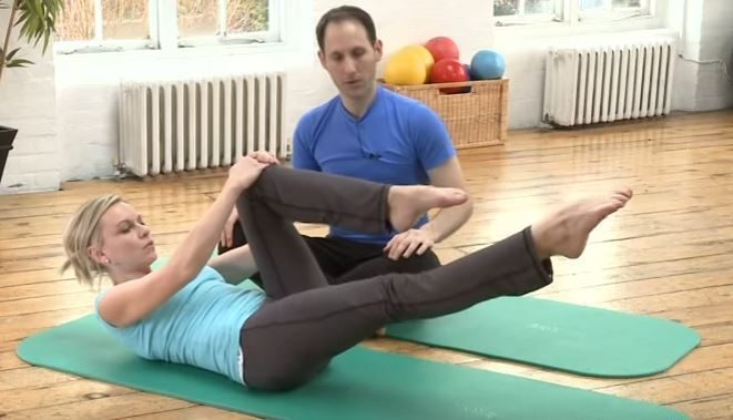 A fitness instructor leads a woman through the single leg stretc