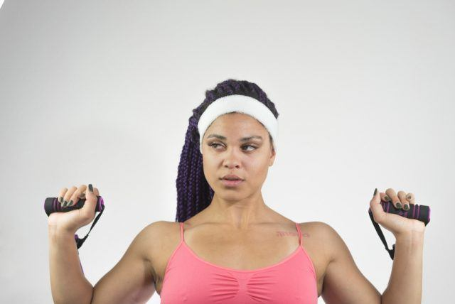 woman uses resistance bands for overhead press