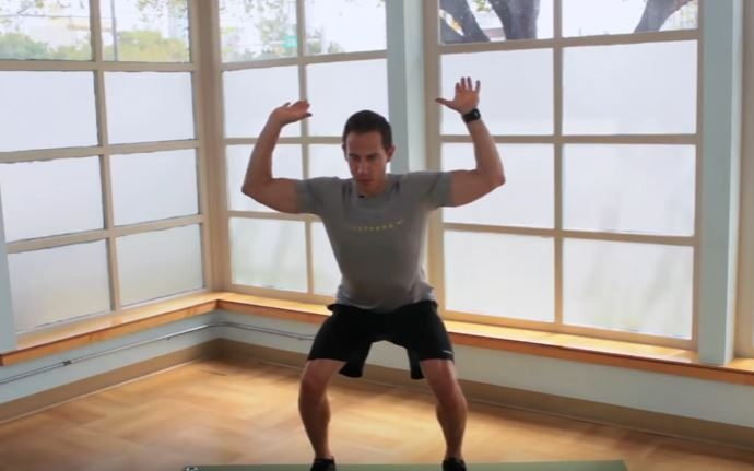 Fitness instructor Jeremy Shore demonstrates a squat and reach