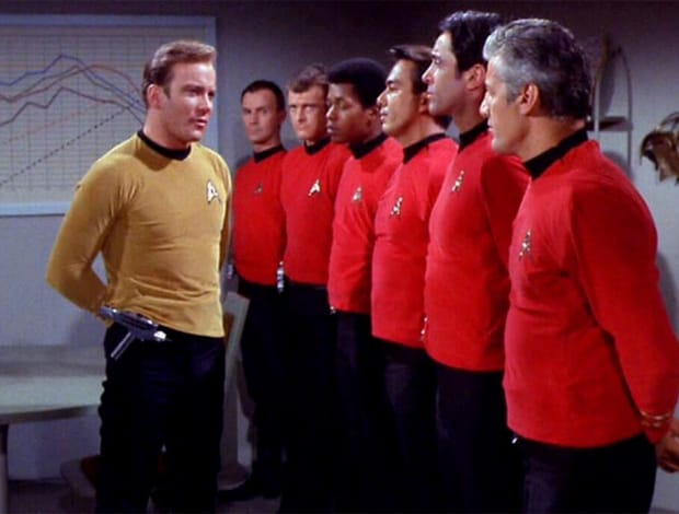 Captain Kirk (William Shatner) stands before a line-up of crewmen in red shirts in a scene from 'Star Trek'