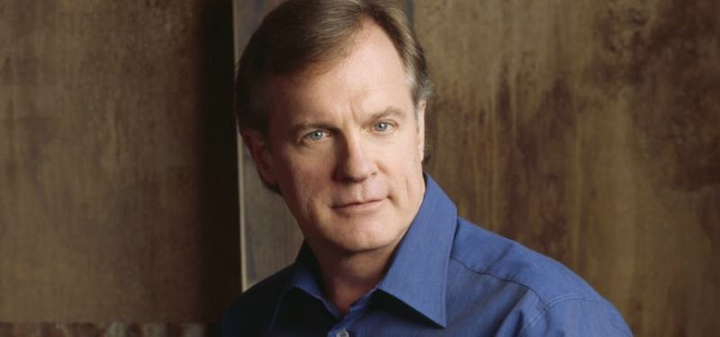 Stephen Collins in a blue shirt looking at the camera