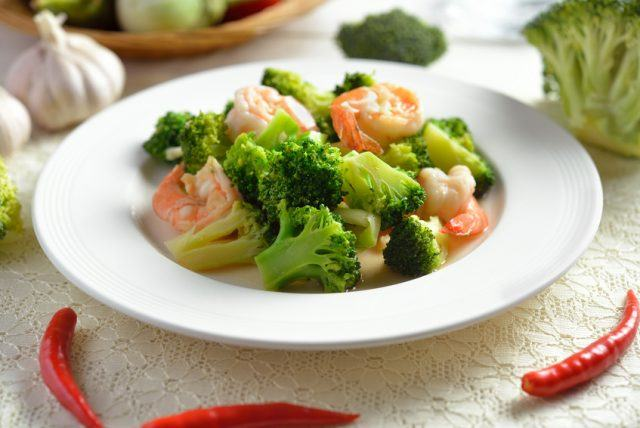 Shrimp and broccoli on a white plate.