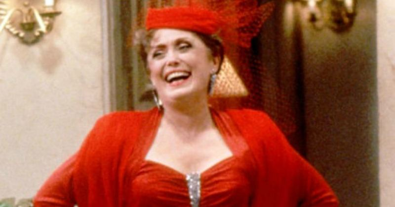 Rue McClanahan laughs in a bright red dress and hat while on the set of The Golden Girls