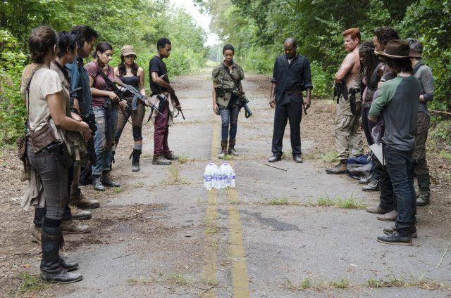 Maggie, Glenn, Eugene, Tara, Rosita, Noah, Sasha, Father Gabriel, Abraham, Michonne, Carol, Rick and Carl stand around bottles of water in a scene from the fifth season of 'The Walking Dead'