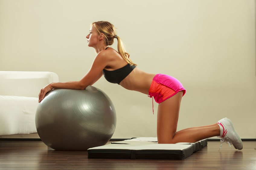 slim woman in sportswear doing fitness exercises with fit ball